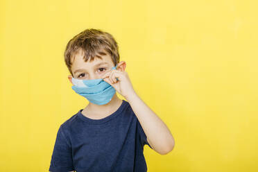 Portrait of cute boy adjusting face mask against yellow background - JRFF04438