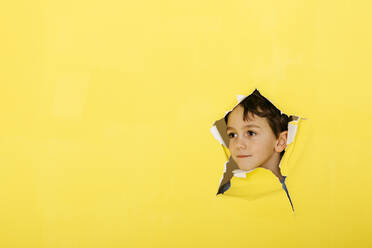 Close-up of cute boy looking away through torn yellow paper - JRFF04447