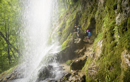 Boy and girl hiking on rock formation under Urach Waterfall in forest - DIKF00496