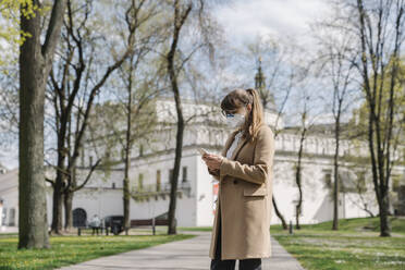 Woman wearing FFP2 mask and using smartphone in a park - AHSF02510
