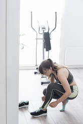 Woman preparing for a workout at home - AHSF02516