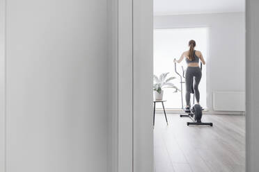 Woman during workout on elliptical trainer at home - AHSF02522
