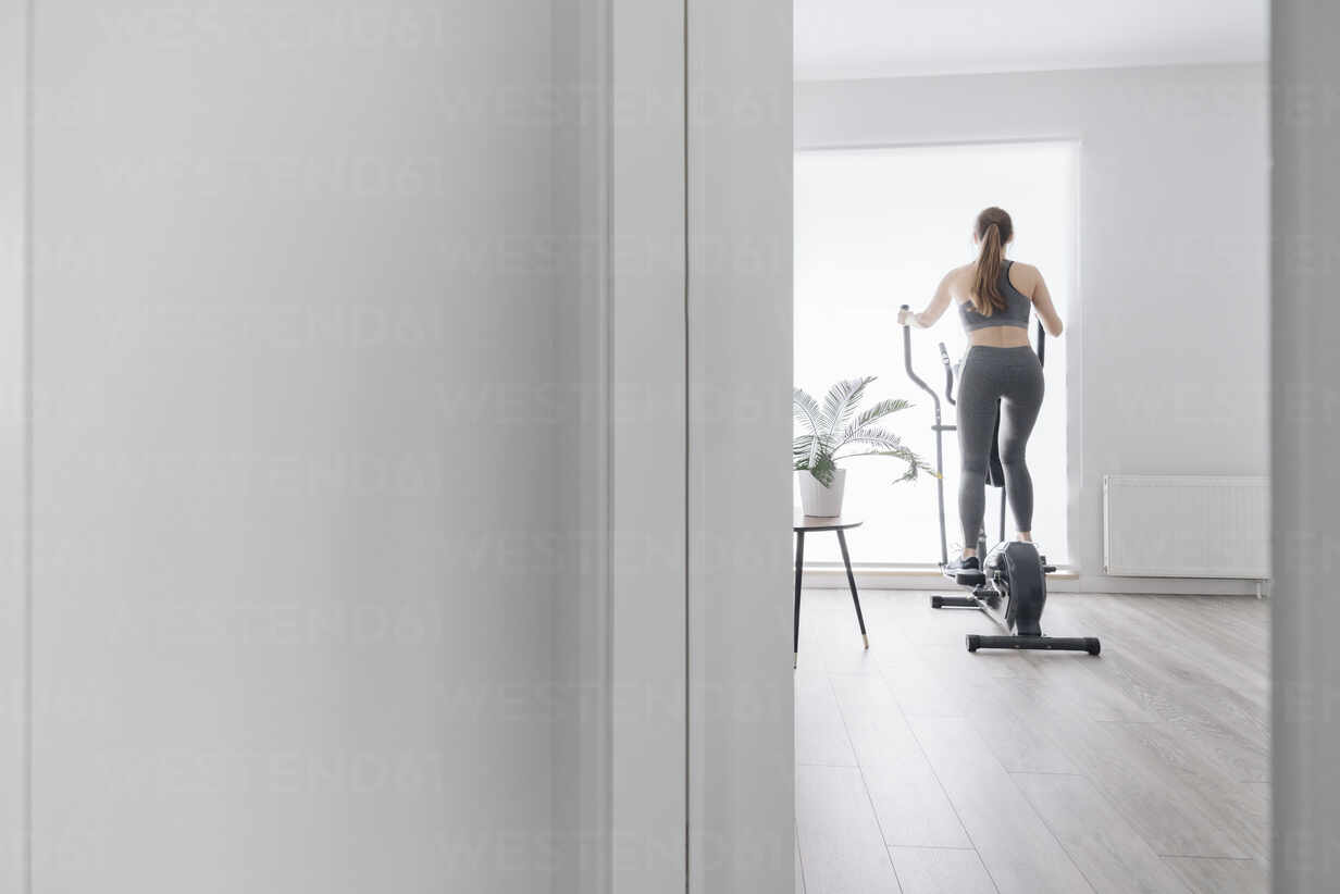 Woman during workout on elliptical trainer at home - AHSF02522 - Hernandez and Sorokina/Westend61