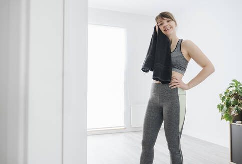 Woman towel sweat after workout at home - AHSF02528