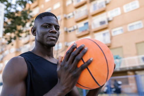 Portrait of young man holding basketball - EGAF00020