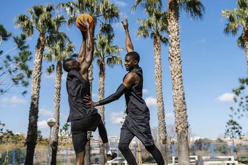 Basketball players playing basketball on court outdoors - EGAF00026
