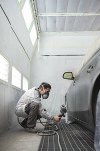 Body painter painting car in paint booth - SNF00018