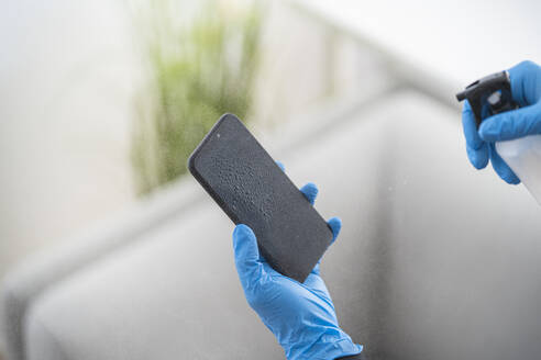 Close-up of woman disinfecting cell phone - SNF00028