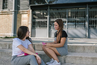 Smiling young female friends talking while sitting on steps at university campus - GRCF00183