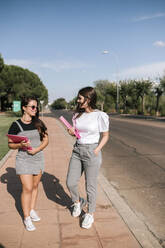 Full length of smiling young female students holding files while walking on footpath at university campus against sky - GRCF00186