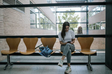 Full length of young female student using smart phone while sitting in university corridor - GRCF00192