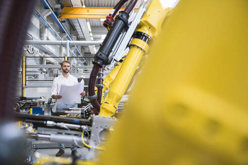 Confident young male engineer looking at robotic arm in factory - DIGF10401