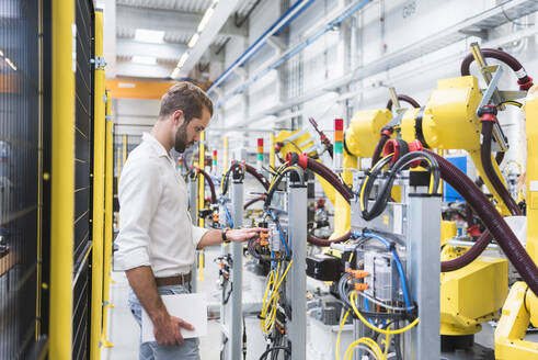 Young male engineer looking at machinery's robotic arm in automated factory - DIGF10410