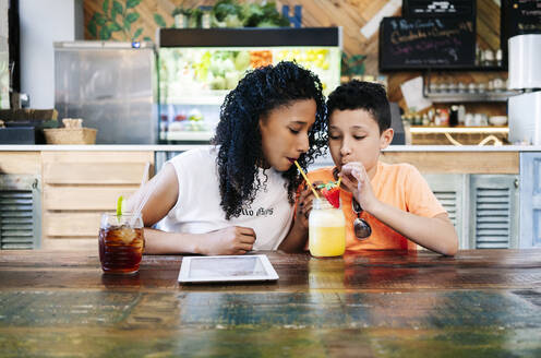 Boy sharing smoothie with mother while sitting at table in restaurant - DGOF00947