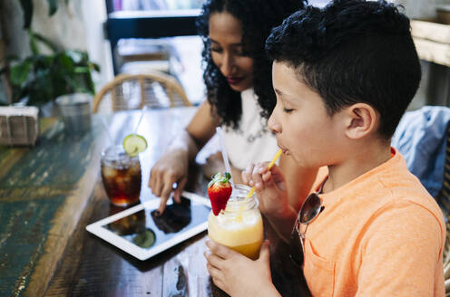 Side view of boy enjoying smoothie by mother sitting with digital tablet at restaurant - DGOF00950
