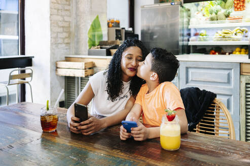 Boy kissing mother while sitting with mobile phones and drinks at restaurant - DGOF00962
