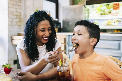 Cheerful young woman feeding son with fork at restaurant - DGOF00965