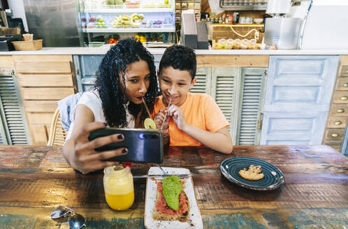 Happy mother and son taking selfie while drinking at restaurant - DGOF00968