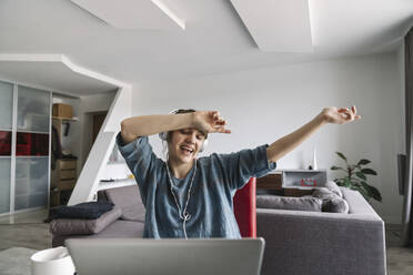 Happy woman wearing headphones and using laptop at home - AHSF02532
