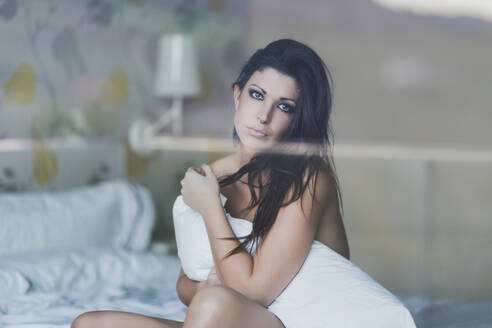 Portrait of beautiful young woman sitting on bed - SNF00099