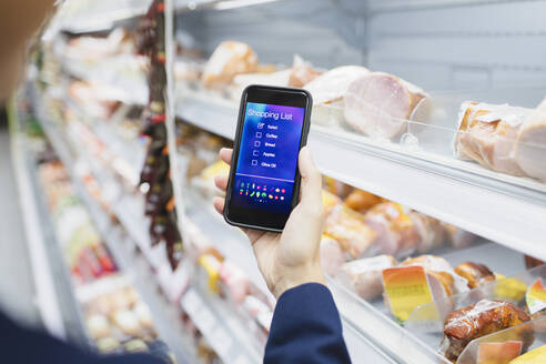 Woman using digital shopping list on camera phone in supermarket - CAIF27295