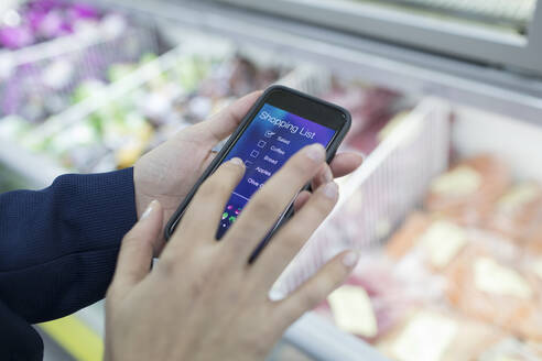 Close up woman using smart phone shopping list app in supermarket - CAIF27352