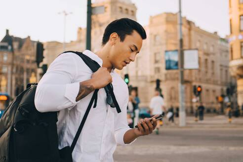 Young man using smart phone while holding bag in city - MASF18140