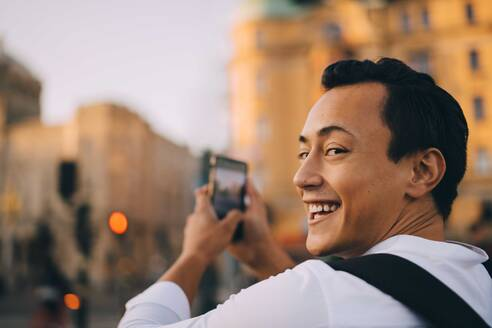 Smiling man looking over shoulder while photographing through phone in city - MASF18143