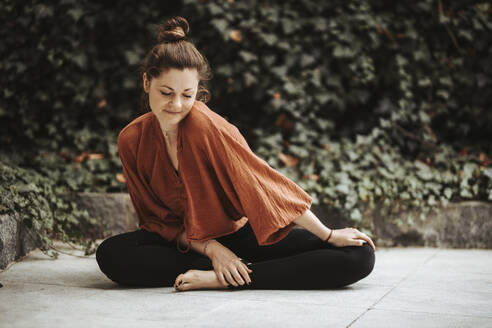 Woman practising yoga in front of wall with ivy - DAWF01400