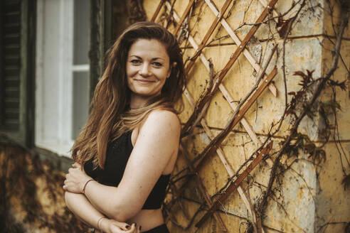 Portrait of sportive woman in front of wall - DAWF01406
