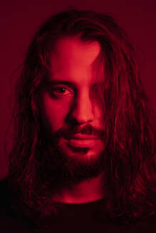 Portrait of red illuminated young man  against red background - EGAF00056