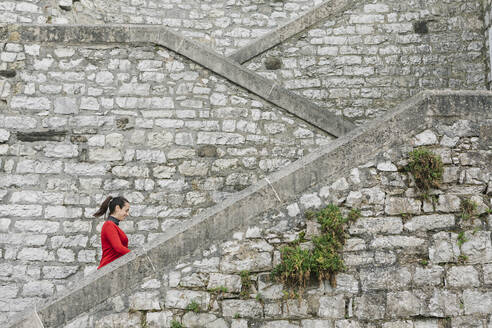 Side view of smiling woman moving up on staircase, Itzurun, Zumaia, Spanish Basque Country, Spain - XLGF00142
