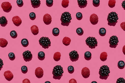 Pattern of raspberries, blueberries and blackberries against pink background - GEMF03695