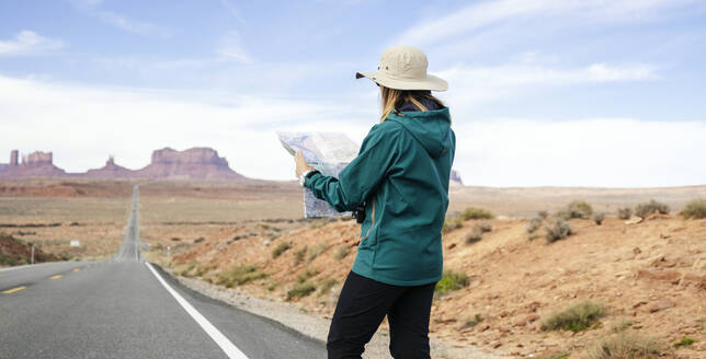 Female tourist reading map while standing on roadside against sky, Monument Valley Tribal Park, Utah, USA - DGOF00987