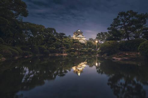Japan, Osaka, Chuo-ku, Osaka Castle reflecting in shiny moat at night - DVGF00089