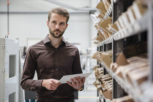 Young businessman using tablet at a shelf in a factory - DIGF10542