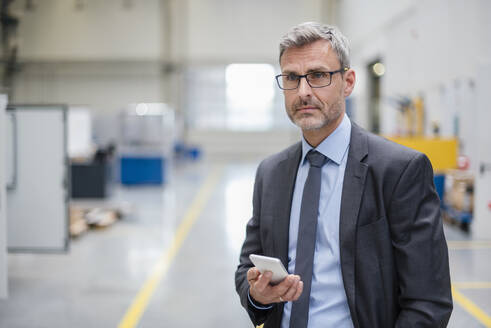 Mature businessman holding cell phone in a factory - DIGF10557