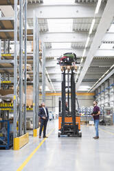 Two men and worker on forklift in high rack warehouse - DIGF10602