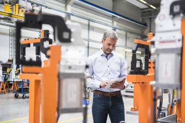 Mature man using tablet on factory shop floor - DIGF10614