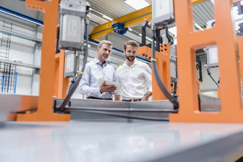 Two men with tablet looking at machine on factory shop floor - DIGF10617