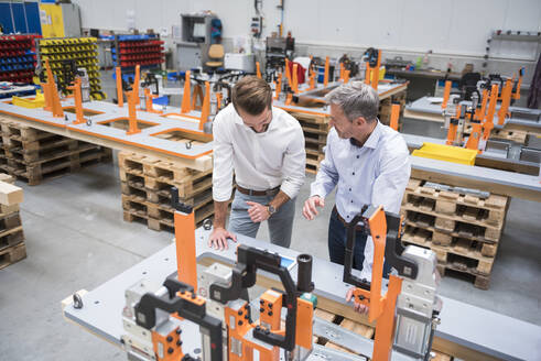 Two men talking on factory shop floor - DIGF10623