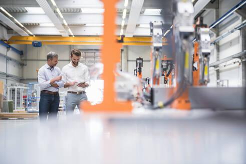 Two men sharing tablet on factory shop floor - DIGF10626