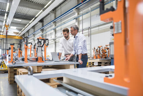 Two men using laptop on factory shop floor - DIGF10629