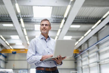 Mature man holding laptop on factory shop floor - DIGF10635