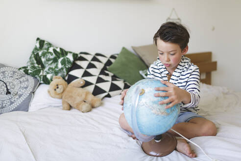 Portrait of little boy sitting on bed with his globe - HMEF00923