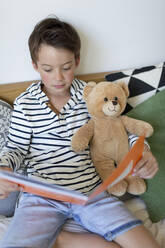 Portrait of little boy sitting on bed with his teddy bear reading - HMEF00932