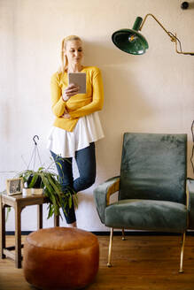 Blond woman standing in living room at home using digital tablet - DAWF01474