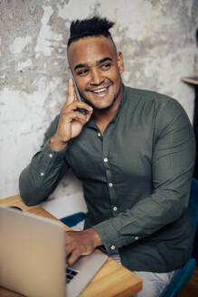 Portrait of smiling young man on the phone working at home office - DAWF01477