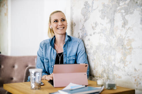 Portrait of smiling blond woman listening music with digital tablet and earphones - DAWF01483