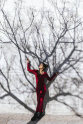 Woman in red dress with dancer pose and tree shadows on  wall - TCEF00619